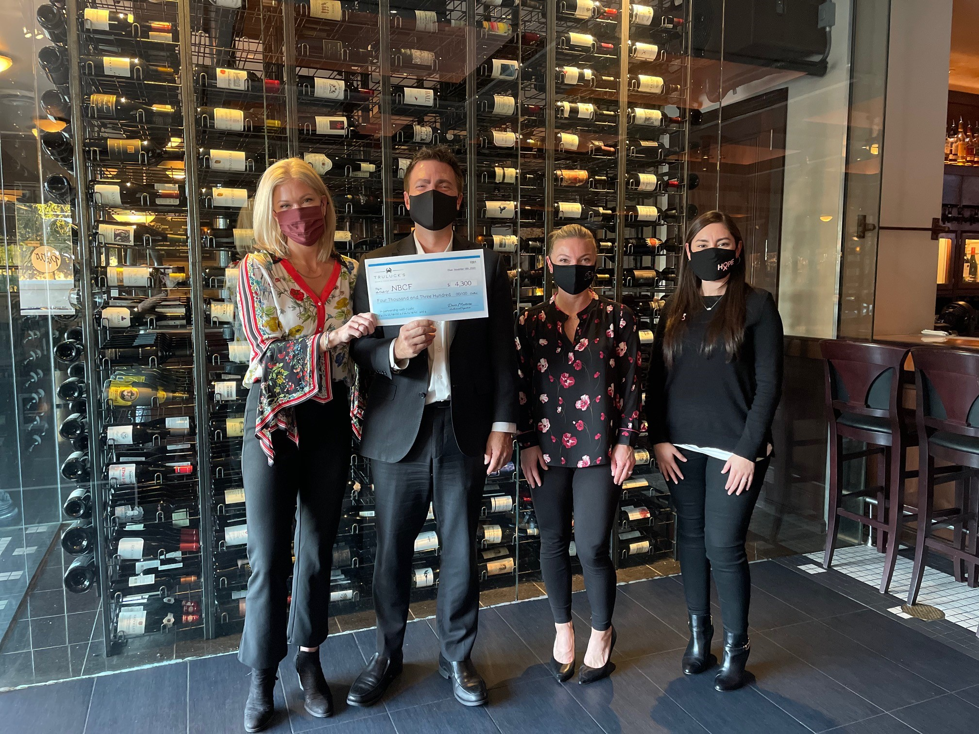 Truluck's team handing off the donation check to National Breast Cancer Foundation in partnership with J. Lohr Carol's Vineyard