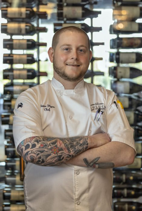 picture of chef partner Shane Flynn in front of the wine wall at the restaurant