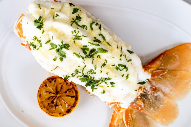 picture of South African lobster tail on a plate dressed in herbs with a lemon wheel