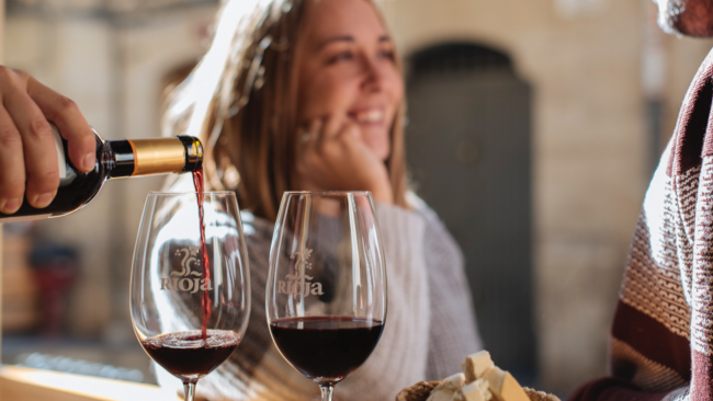 picture of Rioja wine being poured with a lady smiling in the background