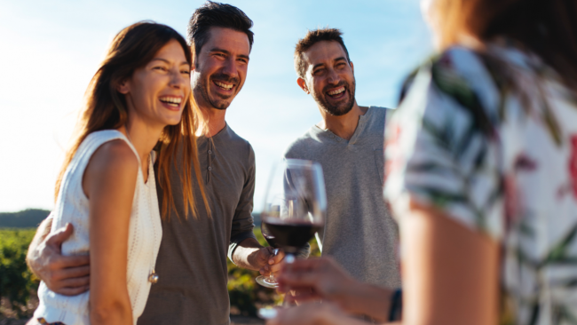 picture of group of people smiling and holding wine glasses in a vineyard