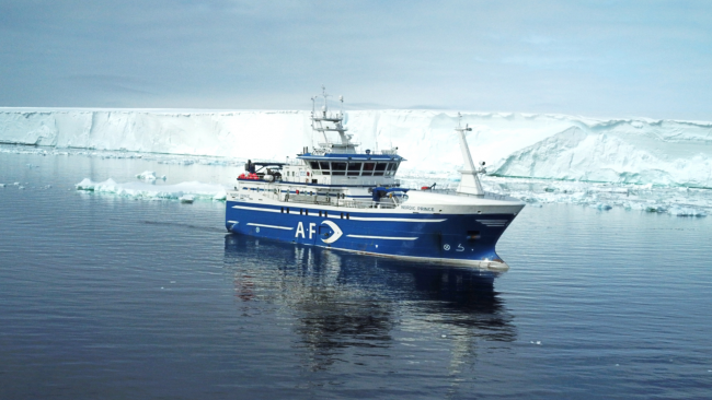 picture of fishing boat near iceberg