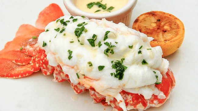 picture of a Truluck's South African lobster tail topped with parsley and with butter dipping sauce and a charred half lemon