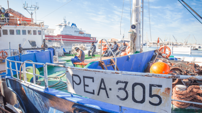 picture of a lobster fishing boat in the dock named PEA 305 with a few fishermen on board